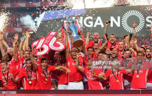 Benfica's Brazilian defender Luisao holds the Portuguese League trophy past teammates as they celebrate winning their 36th title at the end of the...