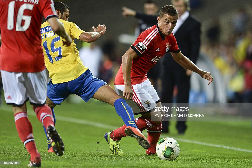 Benfica's Brazilian forward Rodrigo Lima (R) vies with Estoril's Brazilian midfielder Evandro Goebel (2nd L) during the Portuguese league football match GD Estoril Praia vs SL Benfica at the Antonio Coimbra da Mota stadium in Estoril, outskirts of Lisbon, on October 6, 2013. AFP PHOTO / PATRICIA DE MELO MOREIRA