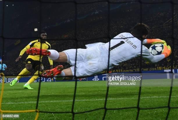 Benfica's Brazilian goalkeeper Ederson Moraes makes a save during the UEFA Champions League Round of 16 2ndleg football match Borussia Dortmund v SL...