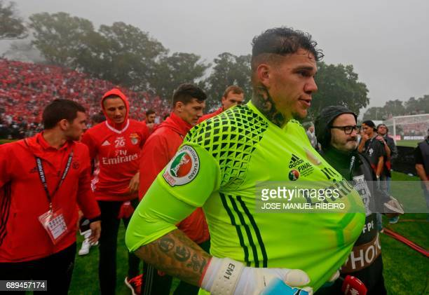 Benfica's Brazilian goalkeeper Ederson Santana keeps the ball under his jersey as he celebrates their victory at the end ofthe Portugal's Cup final...