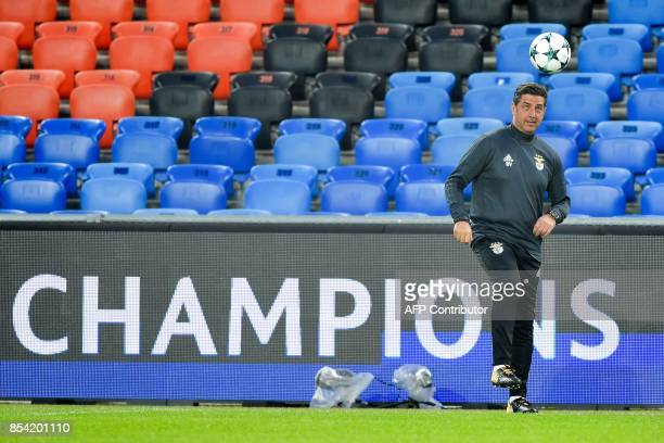 Benfica's coach Rui Vitoria plays with a ball during a training session on the eve of the UEFA Champions league Group A football match between FC...