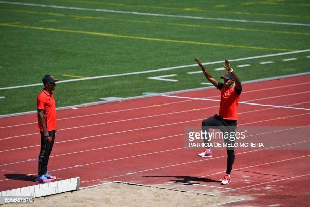Benfica's Cuban triple jumper Pedro Pichardo stands on the track beside his father and coach Jorge Peralta during a meeting with journalists to...