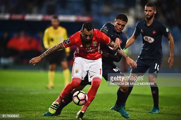 Benfica's Greek forward Konstantinos Mitroglou vies with Belenenses' midfielder Joao Palhinha during the Portuguese league football match between OS...