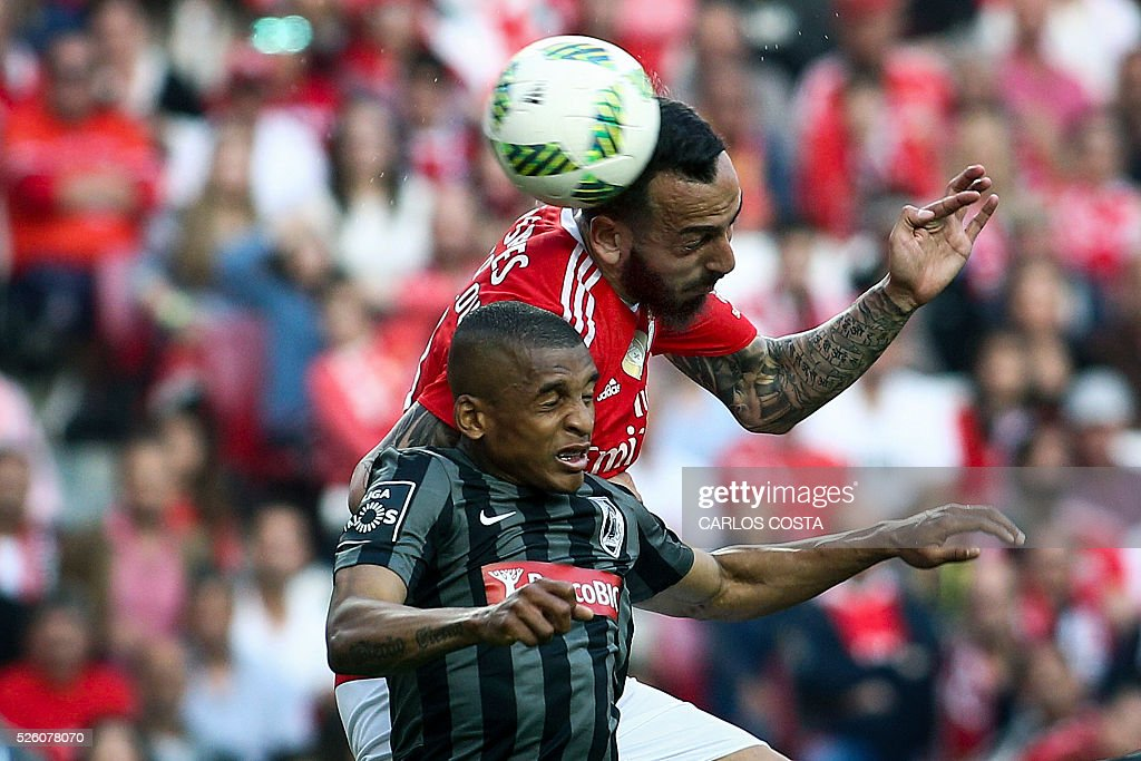 Benfica's Greek forward Kostas Mitroglou (top) vies with Vitoria Guimaraes' Brazilian defender Dalbert during the Portuguese league football match SL Benfica vs Vitoria Sport Clube at the Luz stadium in Lisbon on April 29, 2016. / AFP / CARLOS