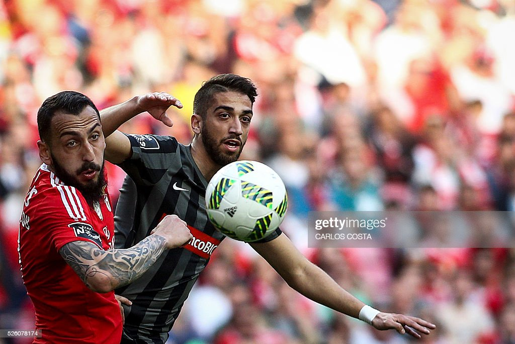 Benfica's Greek forward Kostas Mitroglou (L) vies with Vitoria Guimaraes' defender Josue Sa during the Portuguese league football match SL Benfica vs Vitoria Sport Clube at the Luz stadium in Lisbon on April 29, 2016. / AFP / CARLOS