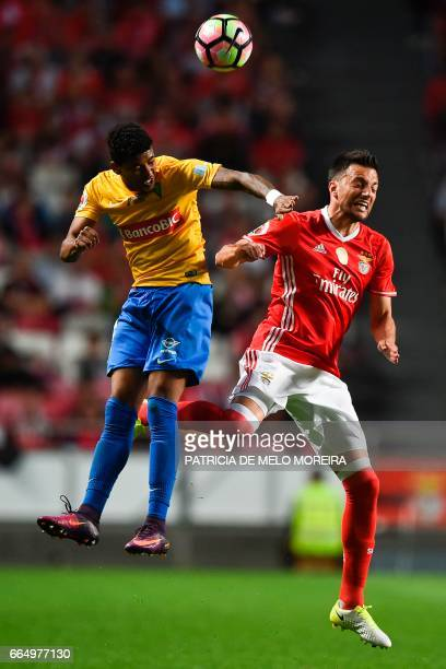 Benfica's Greek midfielder Andreas Samaris heads the ball with Estoril's Brazilian defender Ailton Silva during the Portuguese Cup semifinal second...