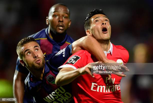 Benfica's Mexican forward Raul Jimenez fights for the ball with Chaves' defender Paulinho beside teammate Brazilian defender Jefferson during the...