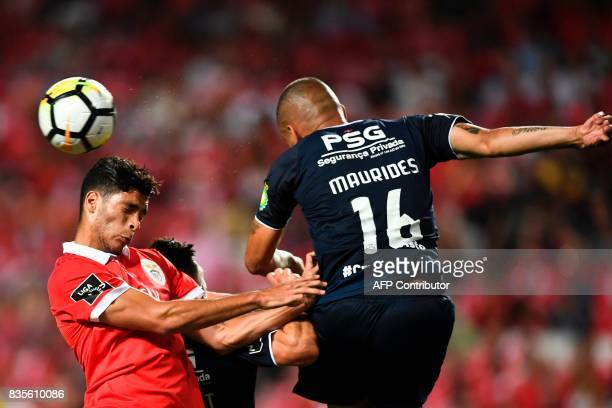 Benfica's Mexican forward Raul Jimenez heads the ball with Belenenses' Brazilian forward Maurides Roque Junior during the Portuguese League football...