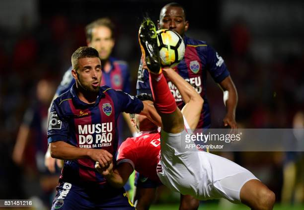 Benfica's Mexican forward Raul Jimenez performs a scissors kick beside Chaves' defender Paulinho during the Portuguese league football match between...