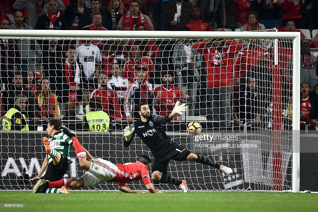 Benfica's Mexican forward Raul Jimenez (C) scores a goal to Sporting's goalkeeper Rui Patricio during the Portuguese league football match SL Benfica vs Sporting CP at the Luz stadium in Lisbon on December 11, 2016. / AFP / PATRICIA