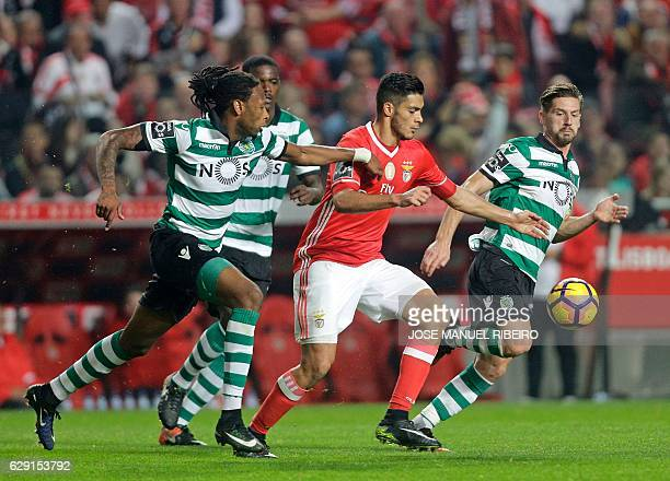 Benfica's Mexican forward Raul Jimenez vies with Sporting's defender Ruben Semedo and midfielder Adrien Silva during the Portuguese league football...