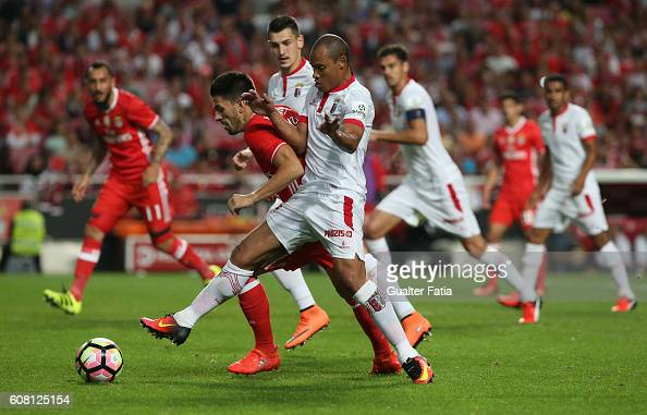 Benfica's midfielder Pizzi tackled by SC Braga's Brazilian defender Baiano during the Primeira Liga match between SL Benfica and SC Braga at Estadio...