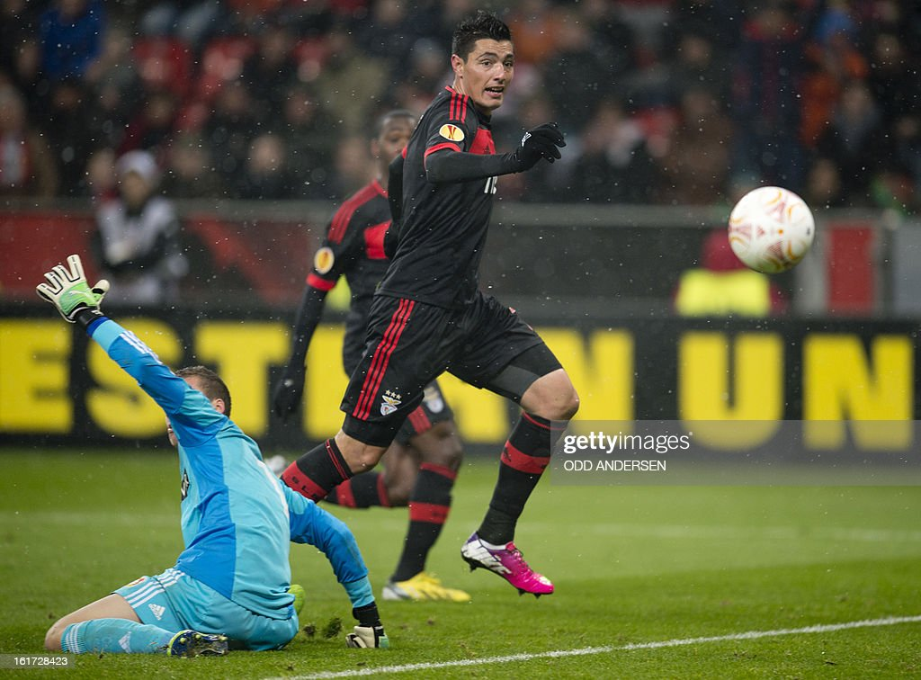 Benfica's Paraguayan forward Oscar Cardozo (R) scores past Leverkusen's goalkeeper Bernd Leno during the UEFA Europa League football match Bayer 04 Leverkusen vs SL Benfica on February 14, 2013 in Leverkusen, western Germany.