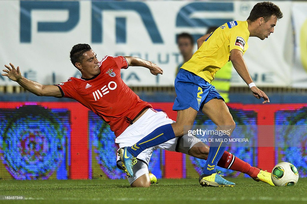 Benfica's Paraguayan forward Oscar Cardozo (L) vies with Estoril's defender Yohan Tavares (R) during the Portuguese league football match GD Estoril Praia vs SL Benfica at the Antonio Coimbra da Mota stadium in Estoril, outskirts of Lisbon, on October 6, 2013. AFP PHOTO / PATRICIA DE MELO MOREIRA