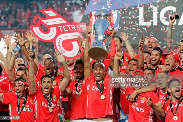 Benfica's players hold the Portuguese League trophy as they celebrate winning their 36th title at the end of the Portuguese league football match SL...