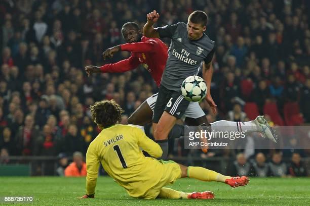 Benfica's Portuguese defender Ruben Dias and Benfica's Belgian goalkeeper Mile Svilar prevent Manchester United's Belgian striker Romelu Lukaku...