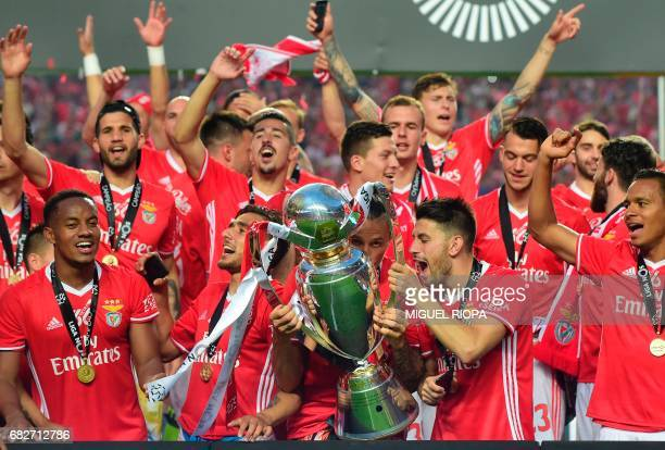 Benfica's Serbian midfielder Ljubomir Fejsa kisses the Portuguese league's trophy with his teammates after winning their 36th title at the end of the...