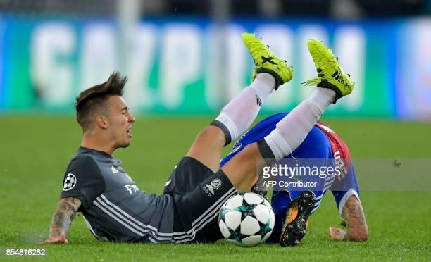 Benfica's Spanish defender Alejandro Grimaldo falls across Basel's Swiss midfielder Renato Steffen during the UEFA Champions League Group A football...