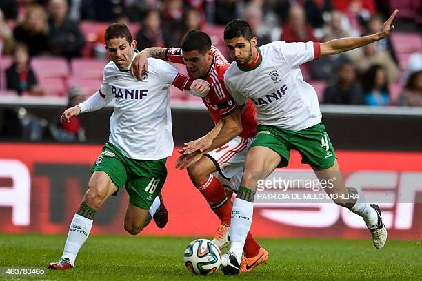 Benfica's Uruguayan defender Maxi Pereira vies with Maritimo's defender Luis Olim and Maritimo's Brazilian defender Igor Branco during the Portuguese...