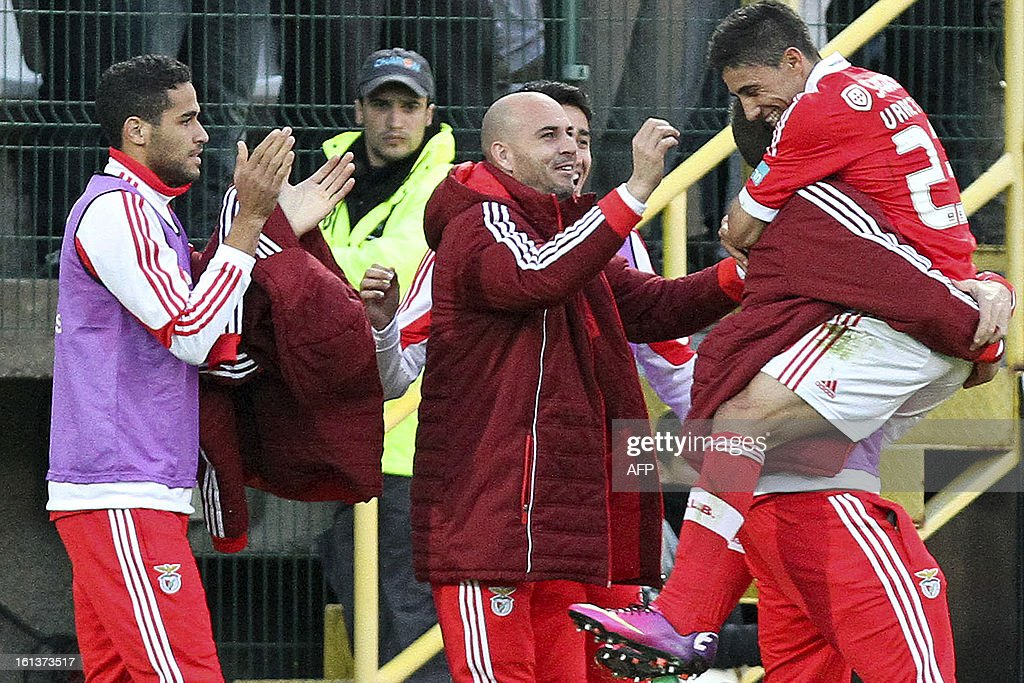 Benfica's Uruguayan midfielder Urreta (R) celebrates with his teammates after scoring during the Portuguese league football match Nacional vs Benfica at Madeira stadium in Funchal on February 10, 2013.