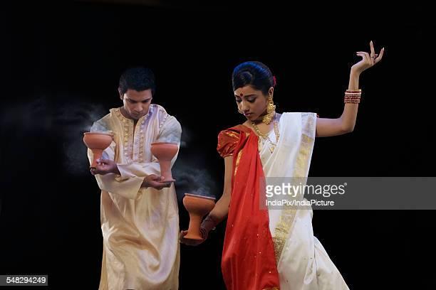Bengali couple doing a Dhunuchi dance