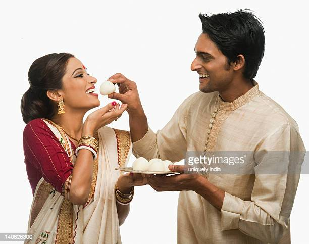 Bengali man feeding a rasgulla to his wife