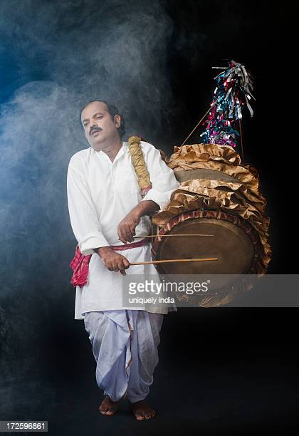 Bengali man playing dhol (A large drum used to play during festival and celebration in India)