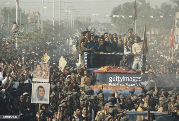 Bengali politician and first President of Bangladesh Sheikh Mujibur Rahman stands with supporters and waves to crowds from the back of a truck as it...