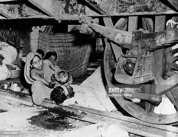 Bengali refugee suffering from malaria and being cared for by his wife under a train wagon in Bangaon around 1947