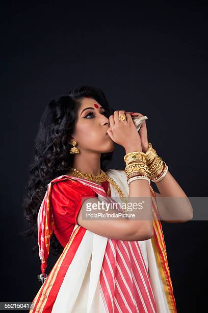 Bengali woman blowing on a conch shell