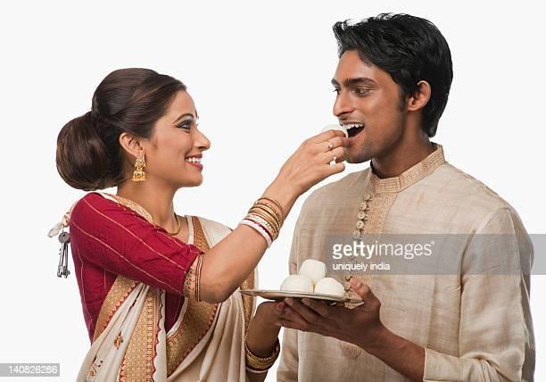 Bengali woman feeding a rasgulla to a man