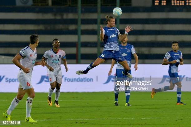 Bengaluru FC player Erik Endel Paartalu heads the ball during the Indian Super League football match between Bengaluru FC and Delhi Dynamos at the...