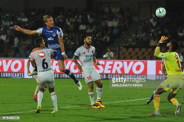Bengaluru FC player Erik Endel Paartalu heads the ball while Delhi Dynamos goal keeper Albino Geovanni Gomes attempts to stop it during the Indian...