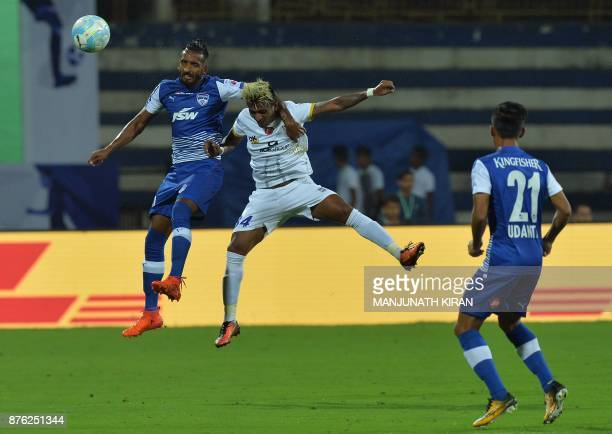 Bengaluru FC player Lenny Rodrigues and Mumbai City FC player Abinash Ruidas jump for the ball during the Indian Super League football match at Sree...
