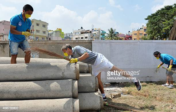 Bengaluru Football Club captain Sunil Chhetri and teammates along with their coach Ashley Westwood clean in the neighbourhood of the football stadium...