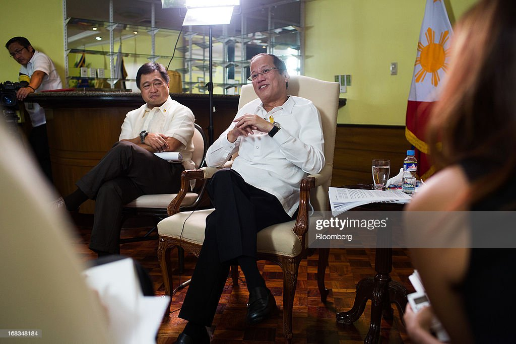 Benigno Aquino, the Philippines' president, center, speaks as Cesar Purisima, Philippine finance secretary, center left, looks on during an interview in the Malacanang Palace compound in Manila, the Philippines, on Wednesday, May 8, 2013. The Philippines, Asia's fastest-growing economy after China, needs to do more to finally lose its decades-old tag as the 'Sick Man of Asia,' according to Aquino. Photographer: Julian Abram Wainwright/Bloomberg via Getty Images