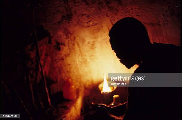 A priest of the egungun secret society prepares for a sacrifice in an egungun temple