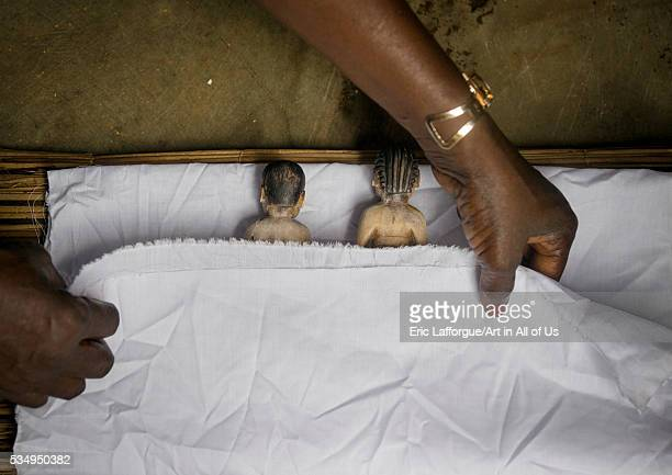Benin West Africa Bopa miss hounyoga putting the carved wooden figures made to house the soul of her dead twins in a bed