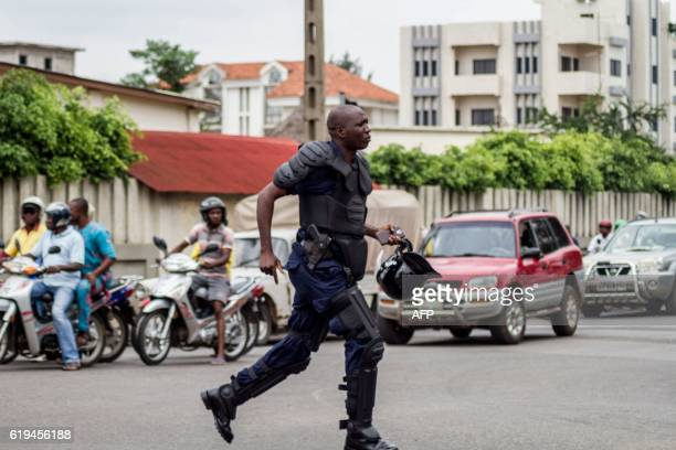 A Beninese antiriot policeman runs in the street as a crowd of supporters of the businessman and former presidential candidate Sebastien Ajavon...