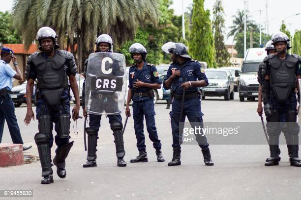 Beninese antiriot policemen stand guard the street as a crowd of supporters of the businessman and former presidential candidate Sebastien Ajavon...