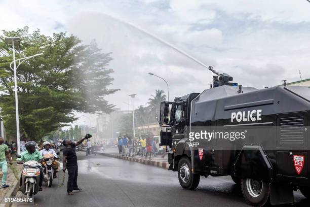 Beninese antiriot policemen use a water cannon vehicle to disperse a crowd of supporters of the businessman and former presidential candidate...