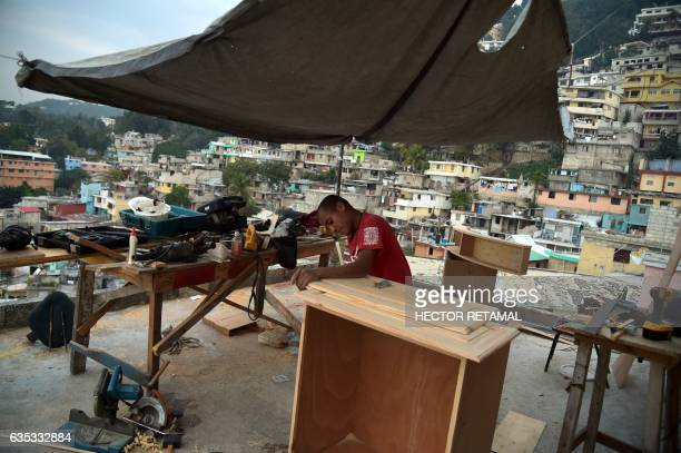 Benito manufactures wooden furniture on the roof of a house in Jalousie neighborhood in the commune of Petion Ville in the Haitian capital...