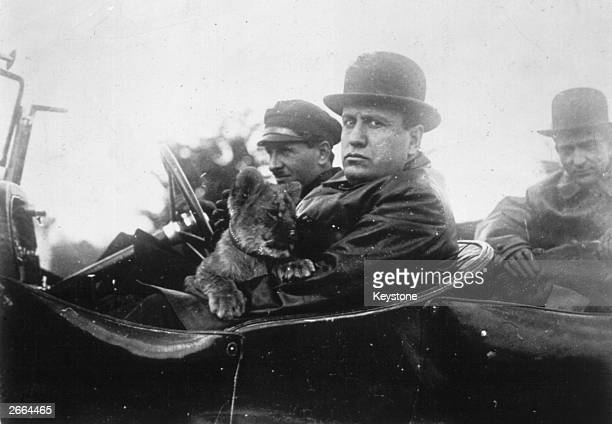 Benito Mussolini going for a drive with his pet lion cub 'Ras' a gift from Aldo Finci