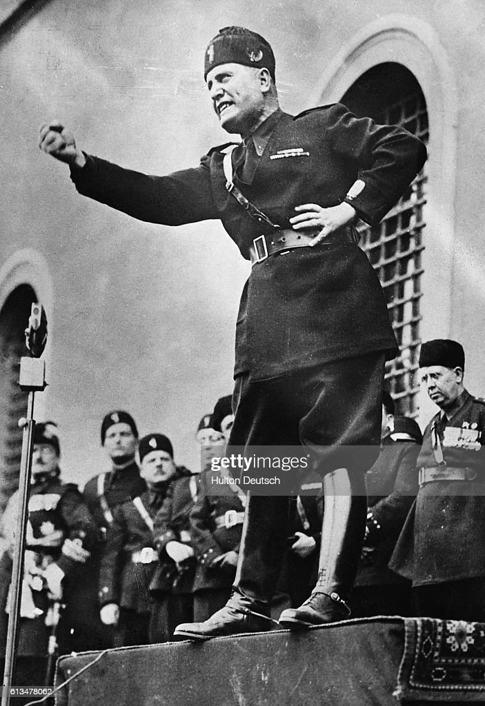 Benito Mussolini, 'Il Duce,' assumes a characteristic pose as he speaks to an audience in Italy in 1934. Mussolini was widely regarded as a hero and a genius in the early days of his dictatorship, and this image of him remained in force until his pacts with Germany brought Italy into World War II, a conflict which shattered the country and reversed all his early efforts.