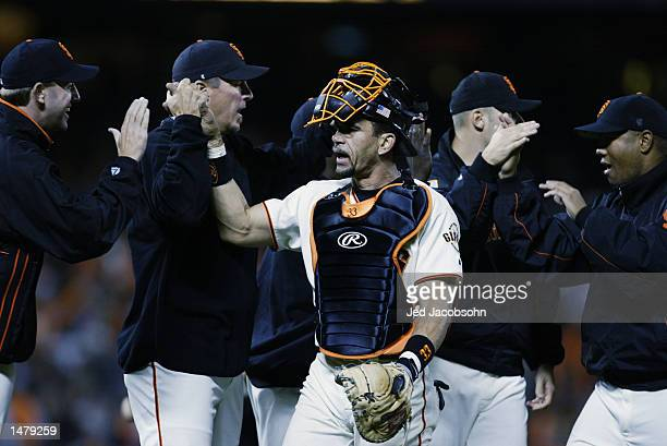 Benito Santiago of the San Francisco Giants celebrates with teammates after winning game four with the score of 43 over the St Louis Cardinals and...
