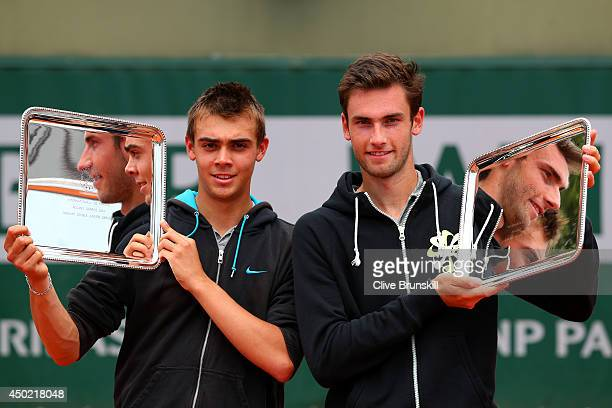Benjamin Bonzi and Quentin Halys of France pose with their trophies following their victory in the boys' doubles final match against Akira Santillan...
