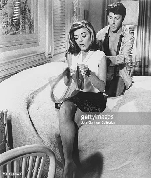 Benjamin Braddock unbuttons the back of Mrs Robinson's blouse in the bedroom during a scene from Mike Nichols' 1967 comedic romance The Graduate