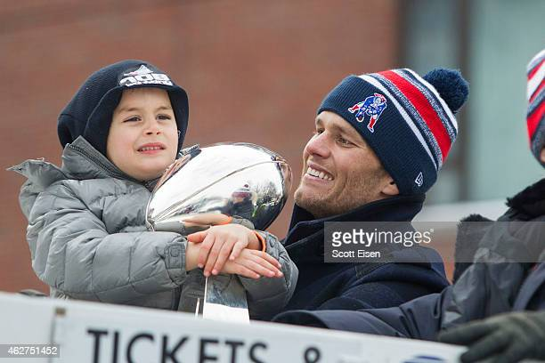 Benjamin Brady holds the Lombardi trophy next to his dad Patriots quarterback Tom Brady on a duck boat during the New England Patriots victory parade...