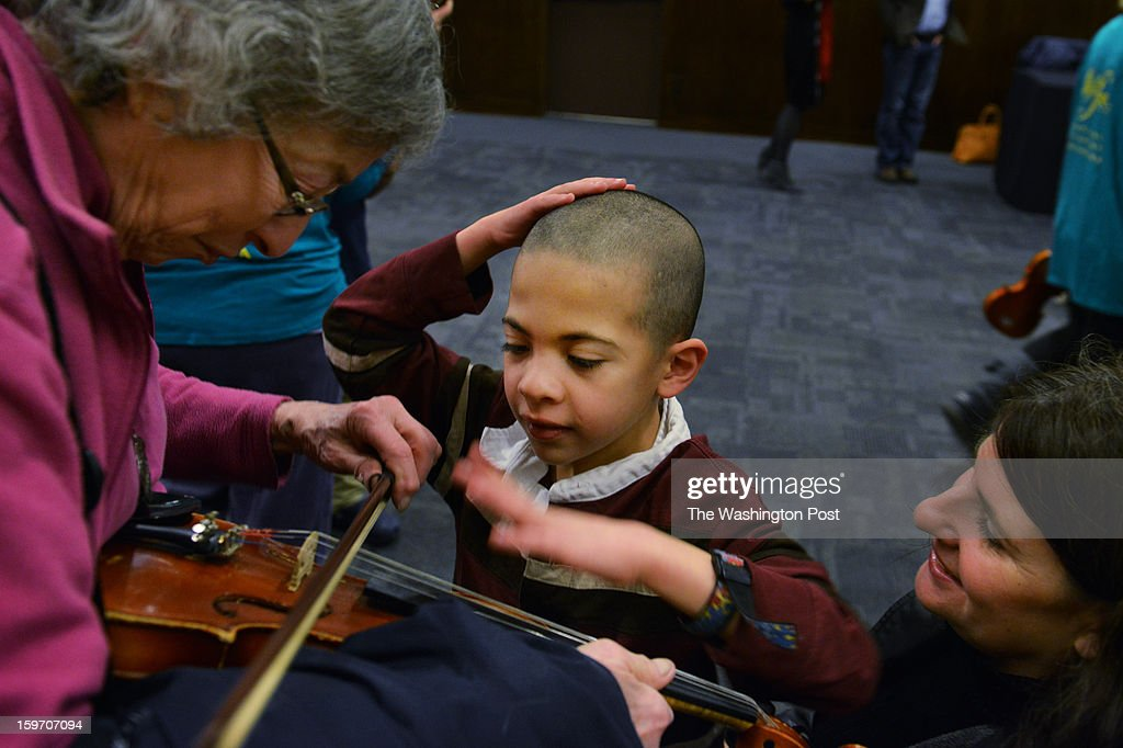 Benjamin Catz-Hollander, 8, who has autism, is intrigued by the violin played by his great aunt Debbie Chassman, L, as Benjamin's mother, Marla Hollander, R, of Old Town Alexandria, sits by during a musical instrument 'petting zoo' at the Kennedy Center on Saturday, January 12, 2012, in Washington, DC. The Kennedy String Quartet--violinists Holly Hamilton and Jane Bowyer Stewart, violist James Deighan, cellist David Teie--gave the sensory-friendly performance for special needs children on the autism spectrum, although all children in attendance do not fall into the autism spectrum category. Hollander said she brought her son to his first event like this to see how he would handle being in such a crowd. The performance is given with the understanding that patrons are free to talk and leave their seats during the performance. There are designated quiet areas within the theater, as well as space throughout the theater for standing and movement. Hollander also called her aunt Debbie Chassman a 'cultural diva' for pushing them out to such events.