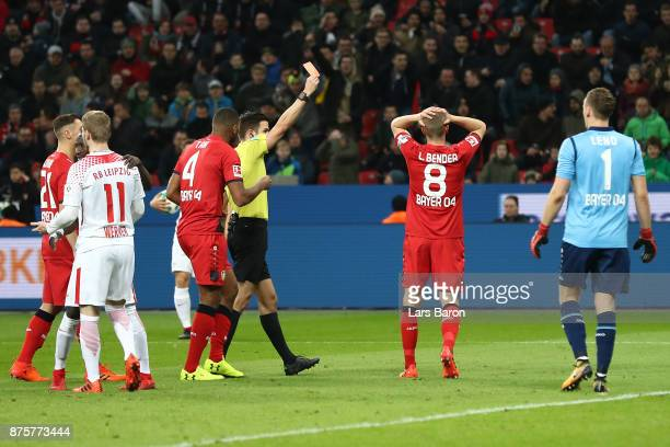 Benjamin Henrichs of Bayer Leverkusen receives a red card from referee Harm Osmers during the Bundesliga match between Bayer 04 Leverkusen and RB...